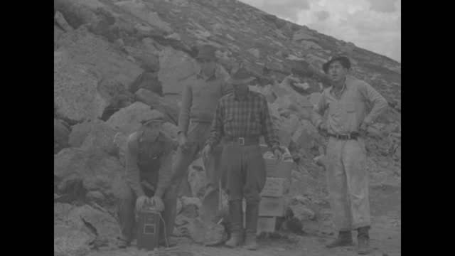 """colorado"" superimposed over mountains / surveyors work on road on top of mountain ridge / surveyor looking through theodolite / steam shovel working... - boulder rock stock-videos und b-roll-filmmaterial"