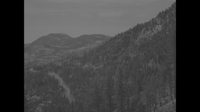 colorado superimposed over pan of wolf creek pass in san juan mountain range in colorado / men walk up side of mountain bearing crates of explosives... - plunger stock videos and b-roll footage
