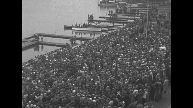 crew over boats rowing across water / crowd watches from shore / crews row across water / audience members watch through binoculars / crews row /... - 1936 stock-videos und b-roll-filmmaterial