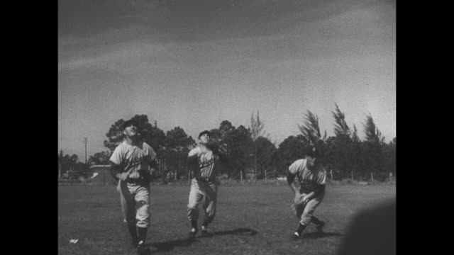 """""""dodgers out to repeat!"""" superimposed over brooklyn dodgers players running onto practice field during spring training in fl / manager chuck dressen... - gabbia di battuta video stock e b–roll"""
