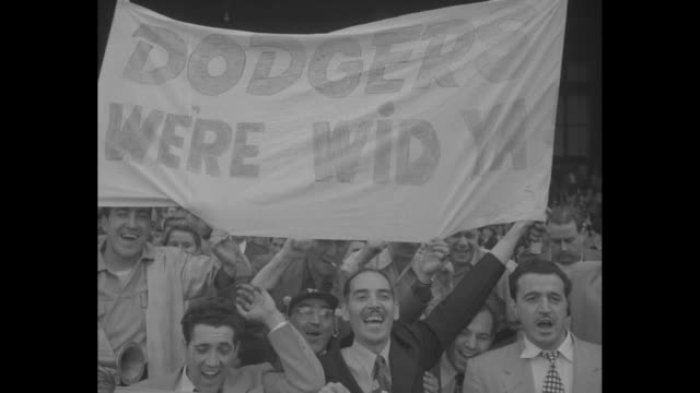 Dodgers Top Phils In 14th superimposed over Dodgers team celebrating in locker room after game / people in stands in Shibe Park hold up sign that...