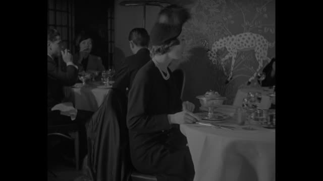 """stockvideo's en b-roll-footage met """"fashions around the clock"""" superimposed over large clock / clock on wall showing one o'clock / people seated at tables for luncheon in dining room... - dining room"""