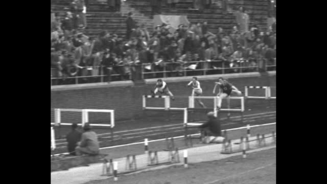 """vídeos y material grabado en eventos de stock de title """"fast stepping youth"""" superimposed over runners racing / overhead wide shot of infield and runners racing on track / crowd in stands / close... - lanzamiento de pesos"""