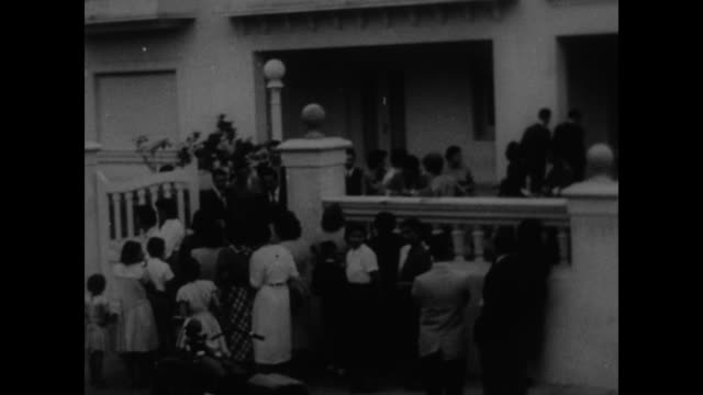 first pictures dictator peron in exile superimposed over women standing on sidewalk in front of juan peron's home / man carries flowers to peron in... - 1955 bildbanksvideor och videomaterial från bakom kulisserna