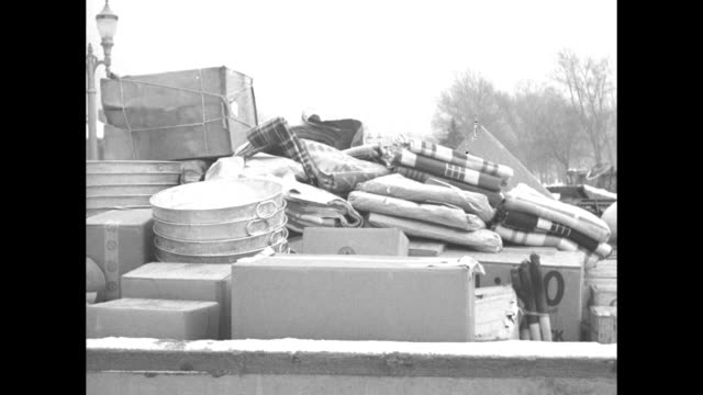 vídeos de stock, filmes e b-roll de title flood and fire superimposed over flood water rushing around structures in fg / relief supplies mostly tubs boxes and blankets / national... - embrace