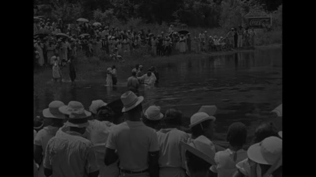 florida superimposed over crowd of africanamericans gathered on bank of river watching people standing in river with preacher / woman walking out of... - preacher stock videos and b-roll footage