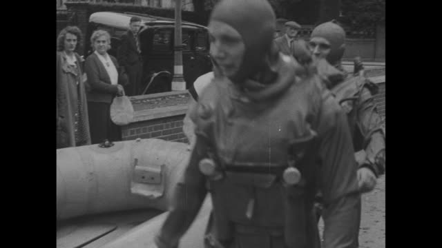 vídeos de stock, filmes e b-roll de title frogmen superimposed over flippered feet walking / vs assistants help them poolside into wet suits helmets flippers / they carry rubber boat to... - diving suit