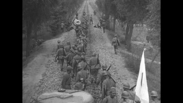 title in japanese superimposed over japanese soldiers marching across bridge over river / montage soldiers lead horses carrying equipment across... - japanese military stock videos & royalty-free footage