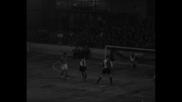 indoor soccer superimposed over action shot of game from behind goal at one end / several action shots of game with one shot of people in crowd /... - the hague stock videos and b-roll footage