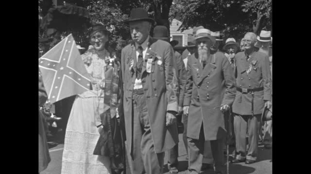 Jackson Miss superimposed over Confederate Army veterans walking outdoors in pairs with women some of whom wear antebellum dress and some of whom are...