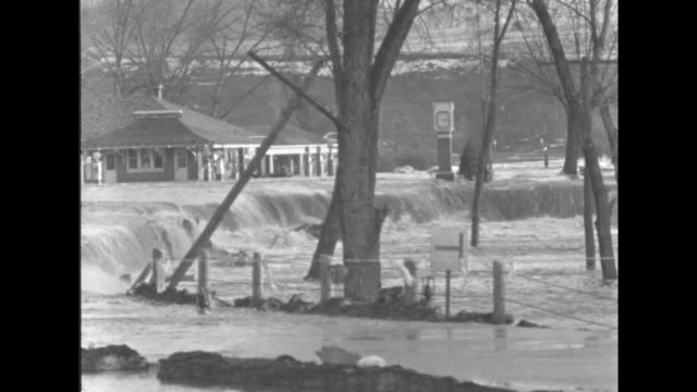 juniata river pa superimposed over floodwater rushing past submerged gas station / vs floodwater rushes past submerged gas station houses / title... - 編集動画点の映像素材/bロール