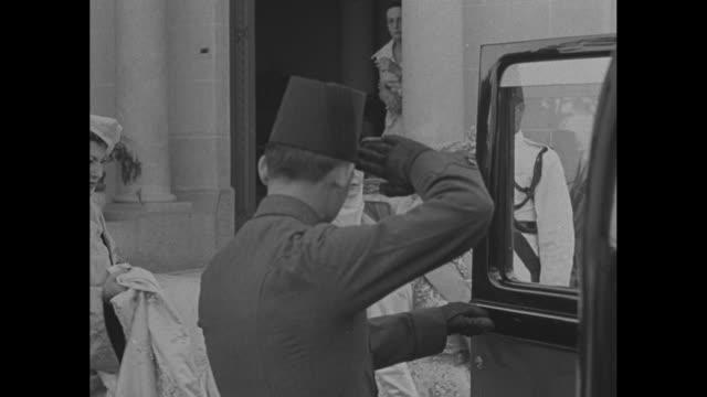 'King Farouk of Egypt Takes 17yrold Bride' superimposed over King Farouk wearing sunglasses standing beside his bride Narriman Sadek / Narriman...