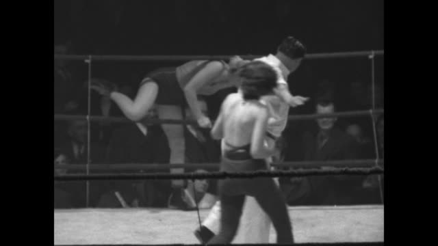 """""""lady killers"""" superimposed on women fighting / vs an elevated view of the women approaching each other then grappling / people in the darkened arena... - mat stock videos & royalty-free footage"""
