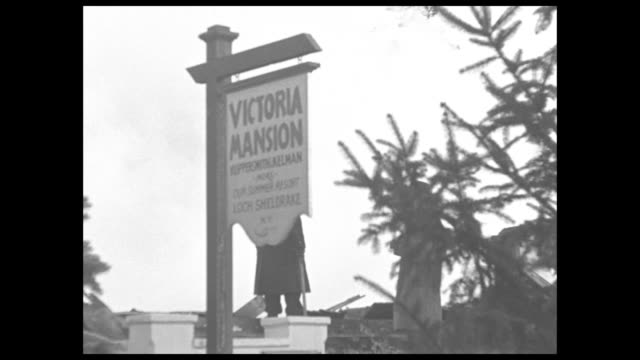 """""""lakewood, n.j."""" superimposed over fire at victoria mansion hotel / sign for victoria mansion hotel in front of firemen on roof / lots of smoke,... - 緊急用具点の映像素材/bロール"""