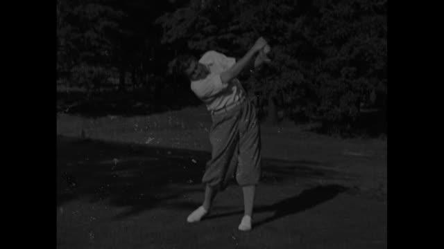 vídeos y material grabado en eventos de stock de lawson little superimposed on the golfer swinging / little's face / he swings in slow motion / swings from sand trap as people look on ball on green... - bandera de golf