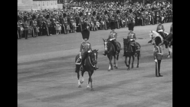 title london superimposed over king george vi wearing bearskin hat and foot guards uniform leading procession of mounted foot guards through the gate... - stallion stock videos & royalty-free footage