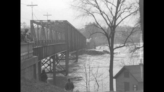 maine paramount news superimposed over power plant flooded by saco river / ms people stand before bridge entrance and watch as debris crashes into... - 1936 stock videos and b-roll footage