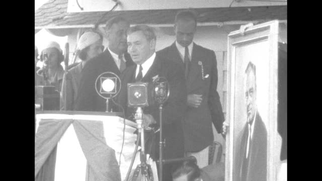 'Mayor Curley of Boston presents a painting' / Boston Mayor James Michael Curley standing at podium speaking Democratic Party presidential candidate...