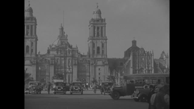 """""""mexico city"""" superimposed over exterior of metropolitan cathedral of the assumption / playwright george bernard shaw holding umbrella and... - ジョージ バーナード ショー点の映像素材/bロール"""