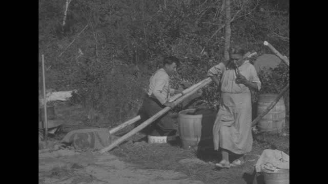 "stockvideo's en b-roll-footage met ""minnesota"" superimposed over native americans harvesting wild rice in the swamp in bagley, minnesota in october 1937 / vs men and women in small... - ijslepel"