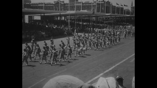 Title Nasser sees Egypt parade military might superimposed on street parade / Egyptian president Gamal Abdel Nasser reviews troops / marching...