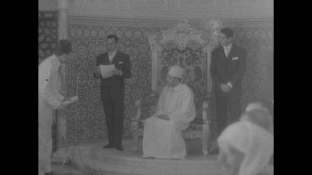 new moroccan cabinet sworn in by sultan superimposed on dignitaries / vs the sultan is seated in elaborately decorated room / andre dubois french... - sultan stock videos and b-roll footage