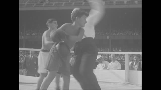 """vídeos de stock e filmes b-roll de """"new york city"""" superimposed on a marching color guard of police / vs a large crowd of rambunctious kids in the grandstands and bleachers / famed... - lightweight"""