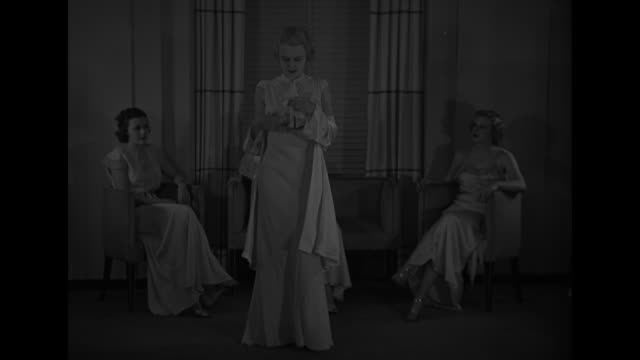 new york city superimposed over model displaying nightgown she has on two models seated watching her fashions are by designer yolande / cu same model... - nightdress stock videos & royalty-free footage