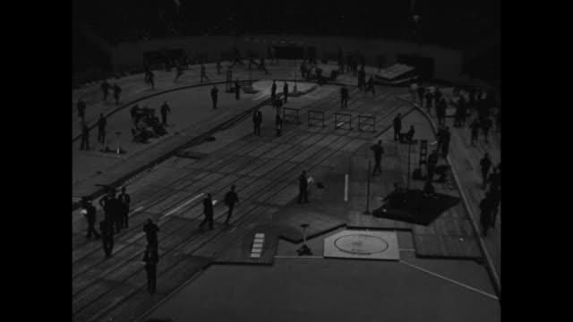 """new york"" superimposed on athletes / vs glenn cunningham running / vs men running in different directions on indoor track; preparations on infield /... - カーテン レース点の映像素材/bロール"