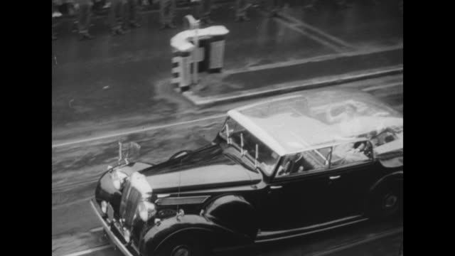 ñNew Zealand Gives Elizabeth Warm Welcomeî superimposed over Elizabeth II reviewing the troops / crowds line the streets as car with Elizabeth II and...