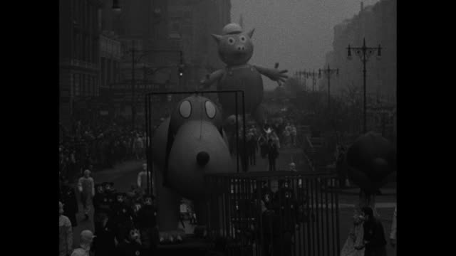 news flashes / giant balloons in parade coming down broadway / giant pig balloon coming down street / children looking on / closer view of giant pig... - disney stock videos and b-roll footage