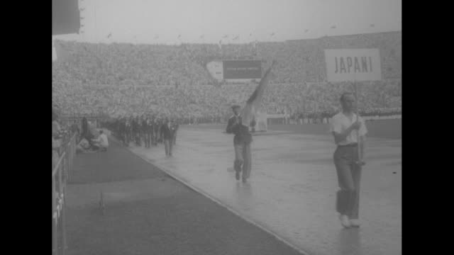 """""""olympic games open!"""" superimposed over olympic stadium filled with crowd / finland's president juho passikivi walks toward seat in stands / crowd in... - all shirts stock-videos und b-roll-filmmaterial"""