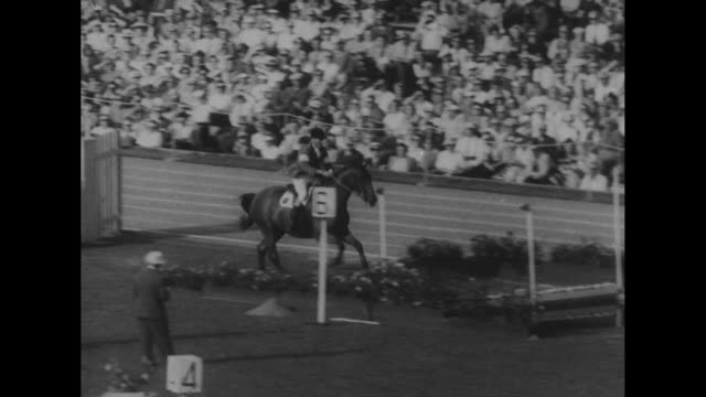 vídeos de stock e filmes b-roll de olympics end superimposed over olympic stadium filled with crowd / ws competitor in steeplechase jumping hurdle /closer view from behind of... - baixar
