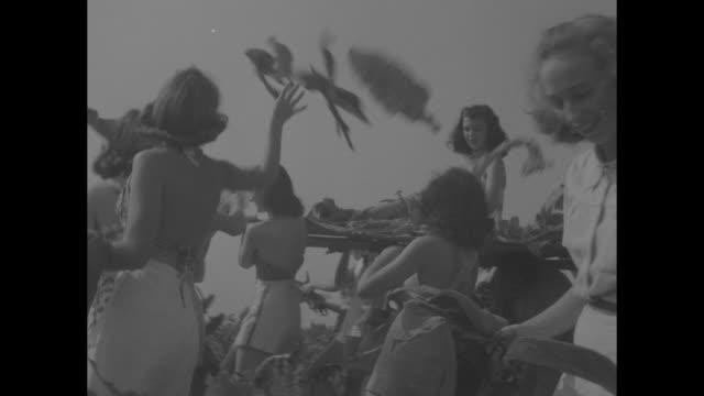 vídeos de stock, filmes e b-roll de dixie farley officiates at tobacco fiesta / four shots of group of women carrying two women on board shaped like tobacco leaf through tobacco field /... - rainha de beleza