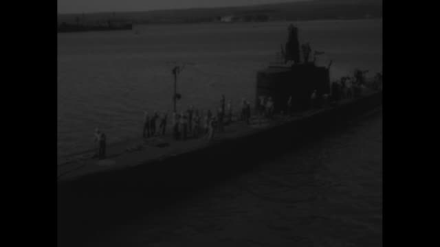 """gold sub - uss trout robs japs of philippine wealth"" / shot from ship of submarine uss trout coming in to dock / crew on deck of submarine as it... - world war ii stock videos & royalty-free footage"