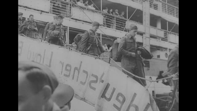 More Prisoners Repatriated Through Spain / shot of Casablanca harbor / shot from below of freed prisoners on ship with swastika on its side / three...