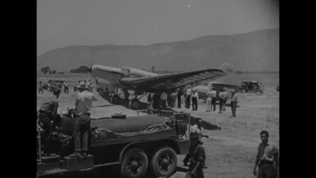 News Flashes / people gathered on airfield in San Jacinto CA around Soviet airplane / closer view of airplane / front view of propeller and engine on...