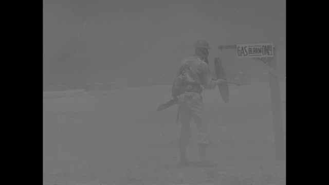 prepared soldiers fight gas at hawaiian school / at chemical warfare school soldier runs across field with gas mask on and sounds gas alarm gas... - ガスマスク点の映像素材/bロール