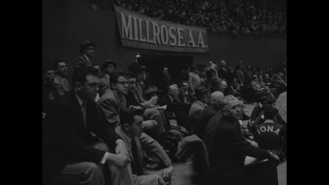 'Sports' / title 'Record For Indoor Mile Tumbles Again' superimposed over runners on track in Madison Square Garden for Millrose Games / runners...