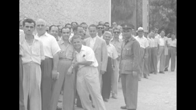 title papagos party wins greek election superimposed over panning wide shot of athens / group of men standing in street waiting to vote / greek... - field marshal stock videos and b-roll footage