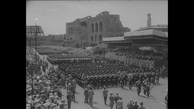 'Parade hails birthday of postwar Italy' superimposed over broad street with large number of marching Italian troops / AERIAL large group of Italian...