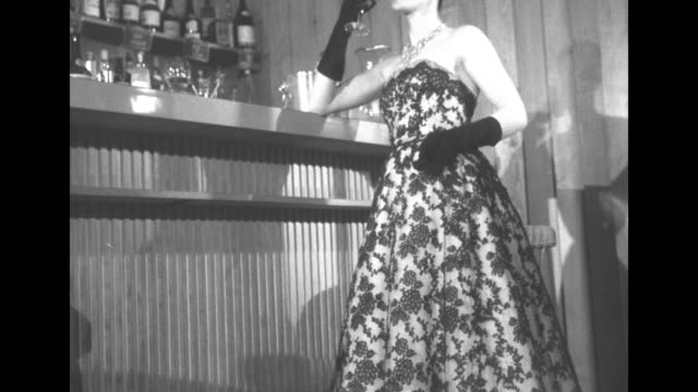 "dior's new dresses"" superimposed over model wearing christian dior evening dress and gloves standing at bar while bartender pours drink for her /... - cut video transition stock videos & royalty-free footage"