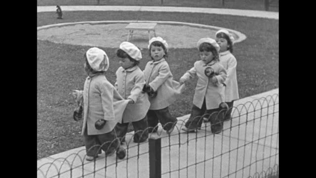 pathe's babies superimposed over cars and bus parked in parking lot / crowd of people who are there to see the dionne quintuplets walk through gate... - girls wearing see through clothes stock videos and b-roll footage