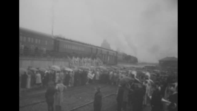 'People In The News' / 10/8/1948 train carrying Pres Harry Truman pulls into Albany crowd waiting / shot of crowd with umbrellas / shot from behind...