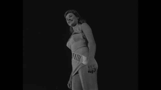 title picking miss universe superimposed on line of women in swimsuits / vs line of women walking on runway tilt up to miss argentina isabel sarli... - concorso video stock e b–roll