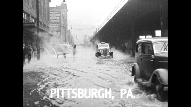 """title """"pittsburgh, pa"""" superimposed over cars moving down flooded street / water pours out of pipes, probably steam rises from flooded street below,... - hands in pockets stock videos & royalty-free footage"""