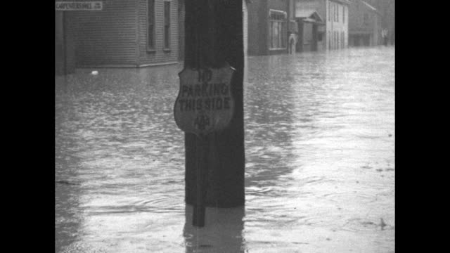"""title """"portsmouth, o."""" superimposed over water pouring over flood wall / closer view / looking down on flooded street in front of houses, men in... - no parking sign stock videos & royalty-free footage"""