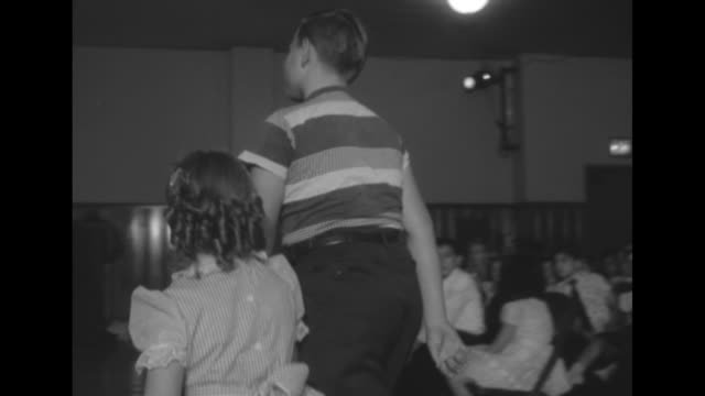 vídeos de stock, filmes e b-roll de title queen of boys is charmer age eight superimposed over stage and audience in auditorium / vs young girls in party dresses sit in audience with... - equipamento doméstico