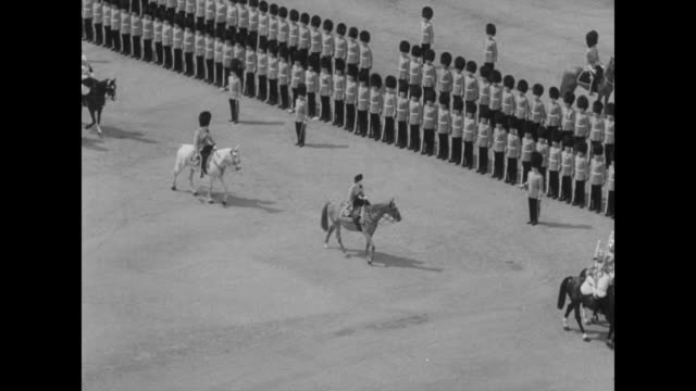 """""""queen reviews trooping of the colors"""" superimposed over elizabeth ii on horseback riding across horse guards parade ground / queen on horseback... - fahnenparade stock-videos und b-roll-filmmaterial"""