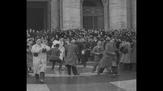 rome superimposed over crowd in front of st peter's / ms crowd in front of st peter's / mussolini and wife walking with other wedding attendees / vs... - benito mussolini video stock e b–roll